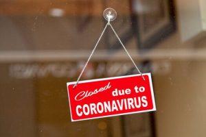 Coronavirus sign on a glass door.